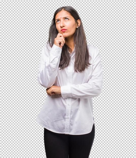 疑って混乱している、考えを考えている、または何かを心配している若いインド人女性の肖像画 Premium Psd
