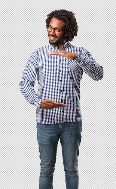 Красивый бизнес афро-американский мужчина держит что-то с руками, показывая продукт, улыбаясь и веселый, предлагая воображаемый объект Premium Psd