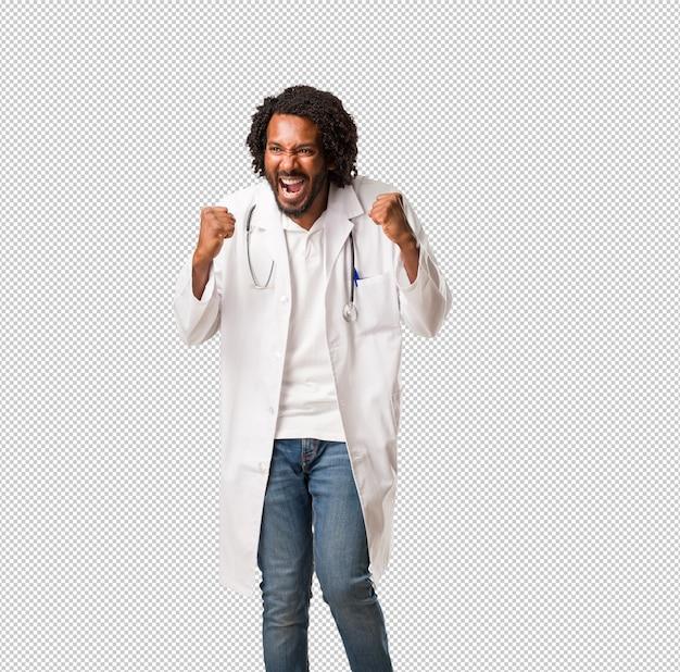 Красивый афро-американский врач очень рад и взволнован, поднимая руки, празднуя победу или успех, выигрывая в лотерею Premium Psd