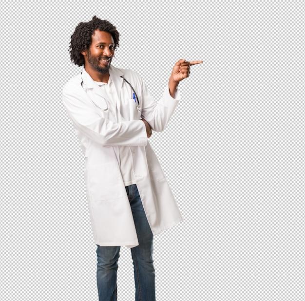 Красивый афро-американский врач, указывая на сторону, улыбаясь удивлен, представляя что-то, естественный и случайный Premium Psd