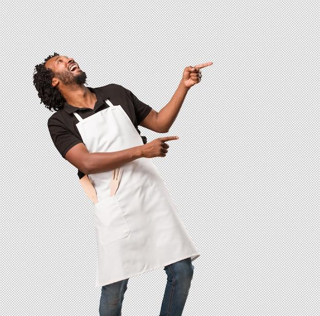 ハンサムなアフリカ系アメリカ人のパン屋、側を指して、驚いた笑みを浮かべて、自然でカジュアルな何かを提示 Premium Psd
