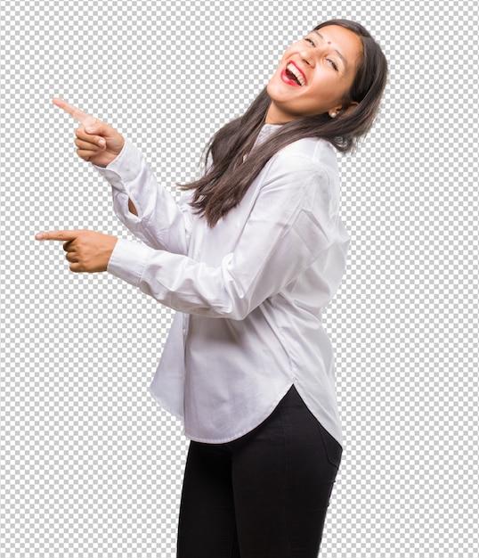 笑みを浮かべて、自然とカジュアルな何かを提示する側を指している若いインド人女性の肖像画 Premium Psd