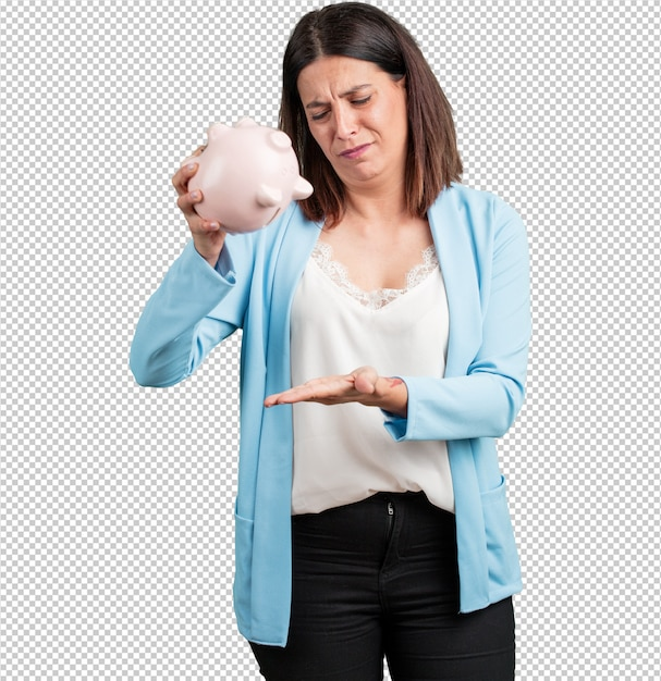 悲しいと失望した中年の女性、子豚の銀行を持っている、お金が残っていない、何かを出そうとしている、怒りと苦悩の顔、貧困の概念 Premium Psd