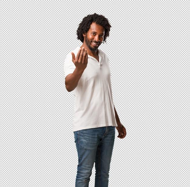 ハンサムなアフリカ系アメリカ人の招待、自信を持って、笑顔で手でジェスチャーを作る、前向きでフレンドリーな Premium Psd