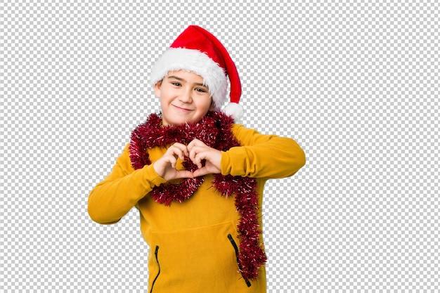 サンタの帽子をかぶってクリスマスの日を祝う少年は笑みを浮かべて、手でハートの形を示します。 Premium Psd