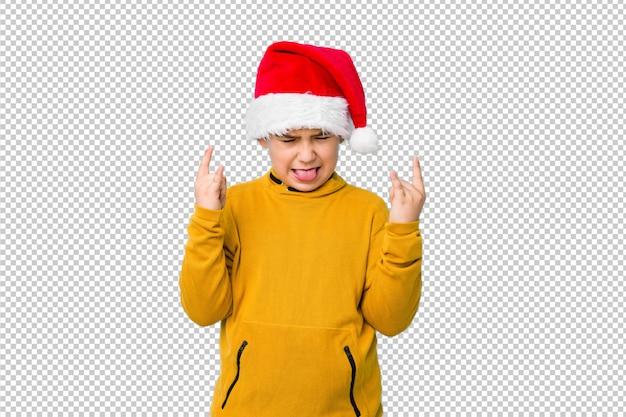 指でロックジェスチャーを示すサンタ帽子をかぶってクリスマスの日を祝う少年 Premium Psd