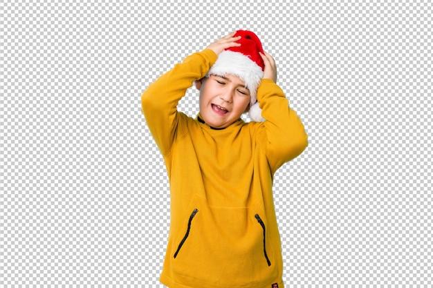 サンタの帽子をかぶってクリスマスの日を祝う少年は、手をつないで喜んで笑います。幸福の概念。 Premium Psd