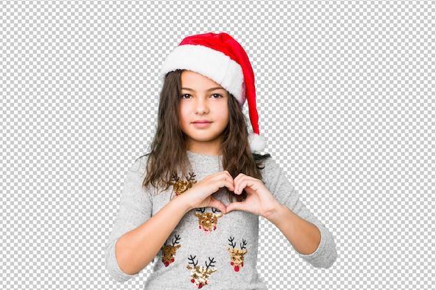 笑顔と手でハートの形を示すクリスマスの日を祝う少女。 Premium Psd
