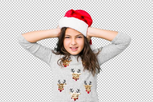 あまりにも大きな音が聞こえないようにしようと手で耳を覆うクリスマスの日を祝う少女。 Premium Psd