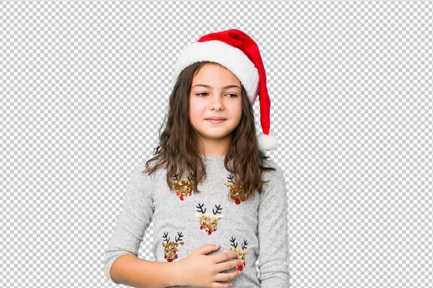 クリスマスの日を祝う少女はおなかに触れる、優しく笑顔、食事、満足の概念。 Premium Psd