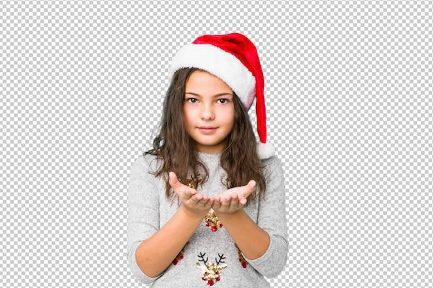 カメラに提供しているヤシの木と何かを保持しているクリスマスの日を祝っている女の子。 Premium Psd