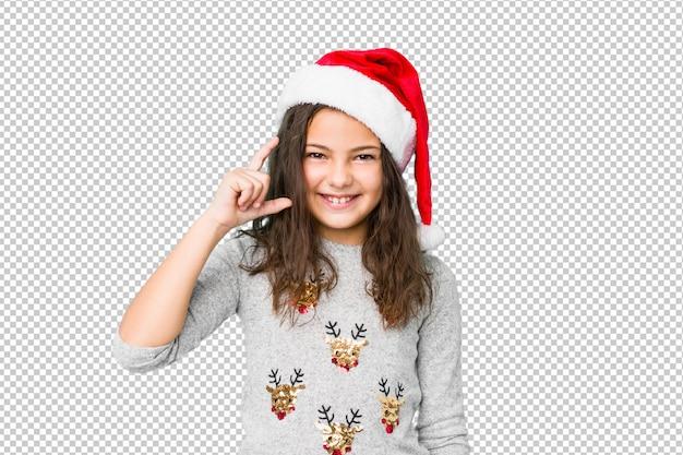 少し人差し指で何かを保持している笑顔と自信を持ってクリスマスの日を祝っている少女。 Premium Psd