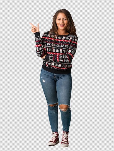 Полная молодая женщина, носить рождественский трикотаж, указывая на сторону пальцем Premium Psd