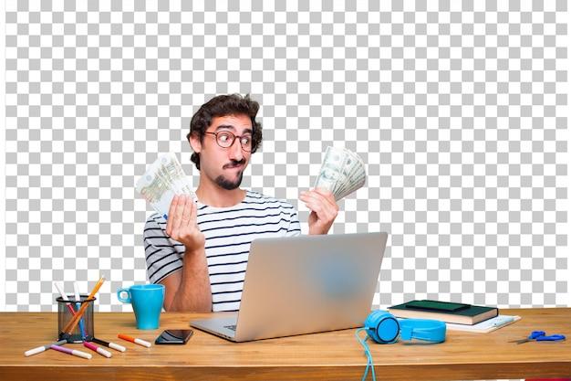 ノートパソコンと支払い、購入またはお金の概念と机の上の若いクレイジーグラフィックデザイナー Premium Psd