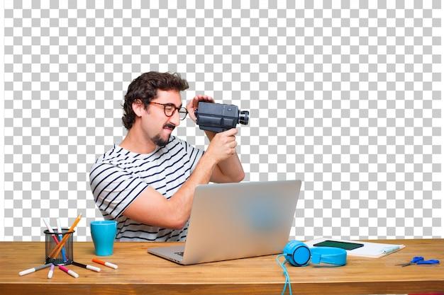 ノートパソコンとビンテージシネマカメラの机の上の若い狂気のグラフィックデザイナー Premium Psd
