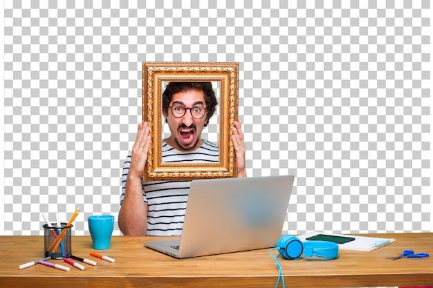 ノートパソコンとフレームを机の上の若いクレイジーグラフィックデザイナー Premium Psd