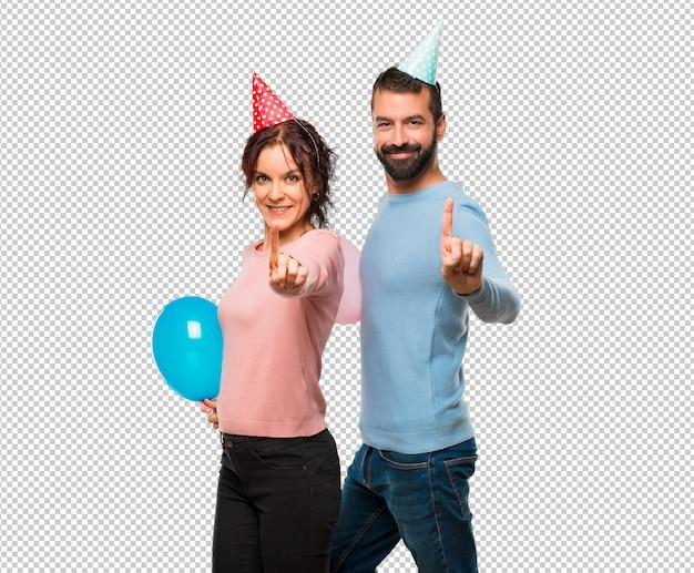 風船と誕生日の帽子とカップルと最高のサインで指を持ち上げる Premium Psd