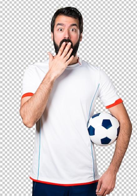 驚きのジェスチャーを作るサッカーボールを保持しているサッカー選手 Premium Psd