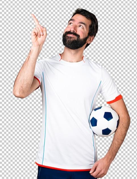 サッカーボールを指さしているサッカー選手 Premium Psd