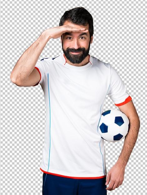 何かを示すサッカーボールを持っているサッカー選手 Premium Psd