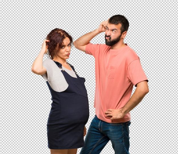 妊娠中の女性と疑いを持ち、頭を傷つけている間に混乱した顔をするカップル Premium Psd