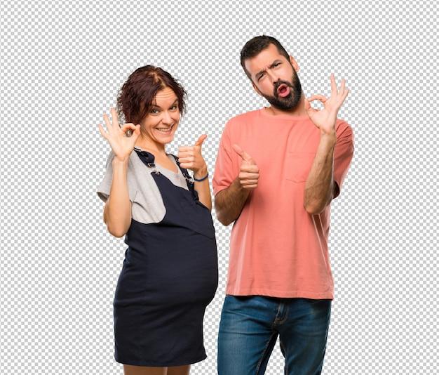 妊娠中の女性と確認サインを交わして、もう一方の手で親指をあげてください Premium Psd