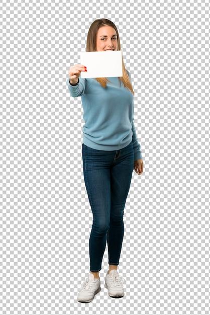 空の白いプラカードを保持している青いシャツと金髪の女性 Premium Psd
