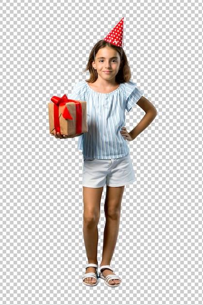 腰に手でポーズをとって贈り物を持って誕生日パーティーで小さな女の子 Premium Psd