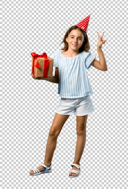 笑みを浮かべて、勝利のサインを示す贈り物を持って誕生日パーティーで小さな女の子 Premium Psd