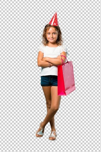腕を組んでギフトバッグを保持している誕生日パーティーの小さな女の子 Premium Psd