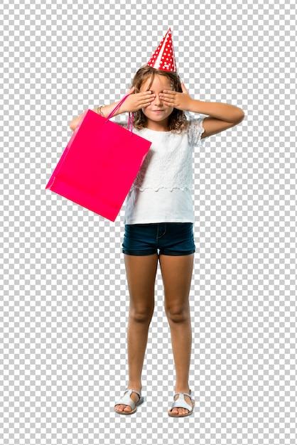 手で目を覆っているギフトバッグを持って誕生日パーティーで小さな女の子 Premium Psd