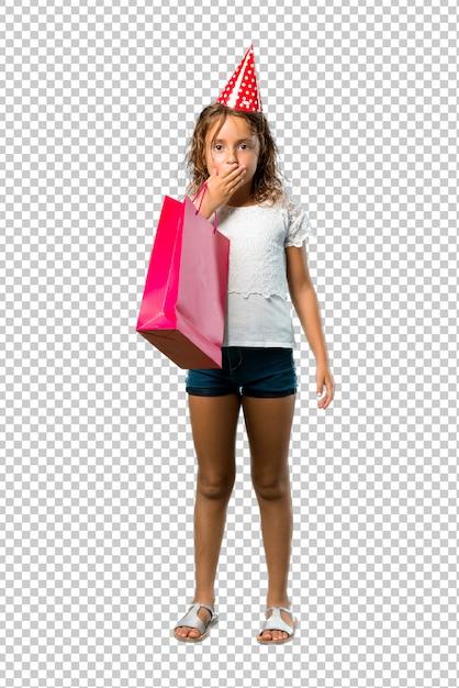 手で口を覆っているギフトバッグを持って誕生日パーティーで小さな女の子 Premium Psd