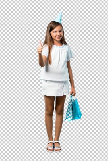ジェスチャーを親指をあきらめると笑みを浮かべてギフト袋を保持している誕生日パーティーで小さな女の子 Premium Psd