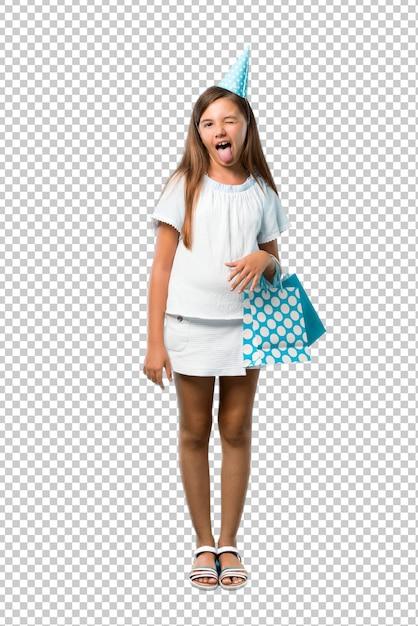変な表情を持つカメラで舌を示すギフトバッグを持って誕生日パーティーで小さな女の子 Premium Psd