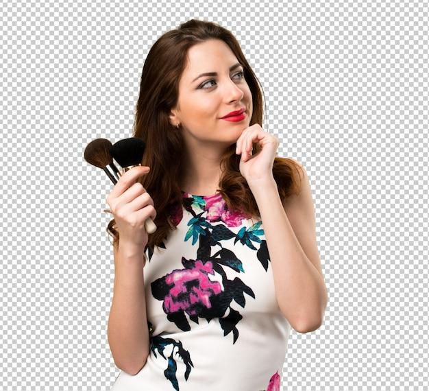 化粧筆を考えて幸せな美しい若い女の子 Premium Psd