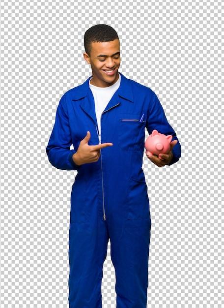 Молодой афро-американский рабочий мужчина держит копилку Premium Psd