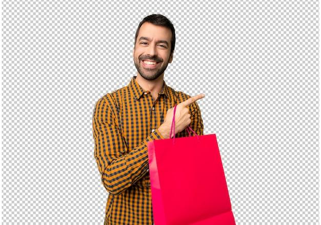 横位置で側に指を指している買い物袋を持つ男 Premium Psd
