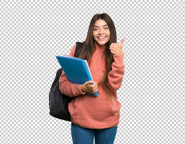 Молодая женщина студента держа тетради показывая одобренный знак и большой палец руки вверх показывать Premium Psd