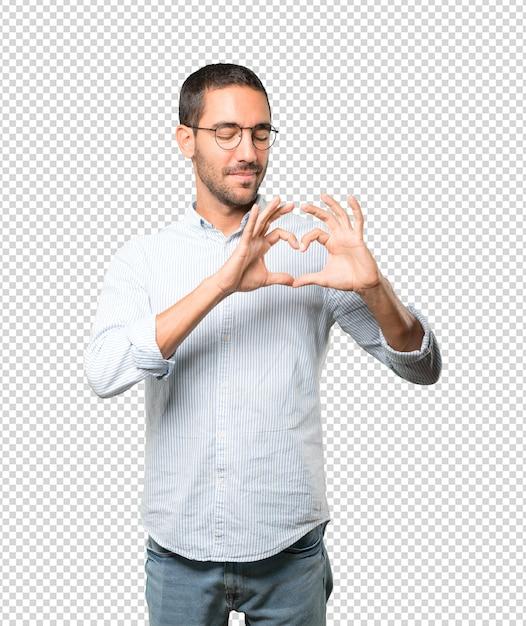 Счастливый молодой человек делает жест любви своими руками Premium Psd