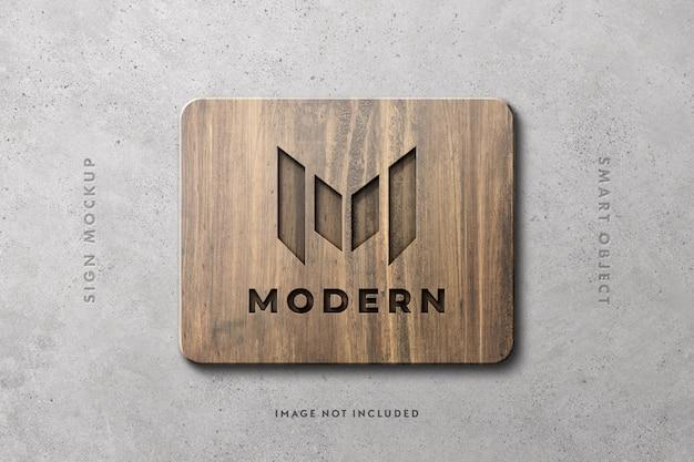 Деревянный знак логотип макет на бетонной стене Premium Psd