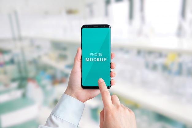 手でスマートフォンモック。バックグラウンドでの研究室。病院アプリのプレゼンテーションのコンセプト Premium Psd