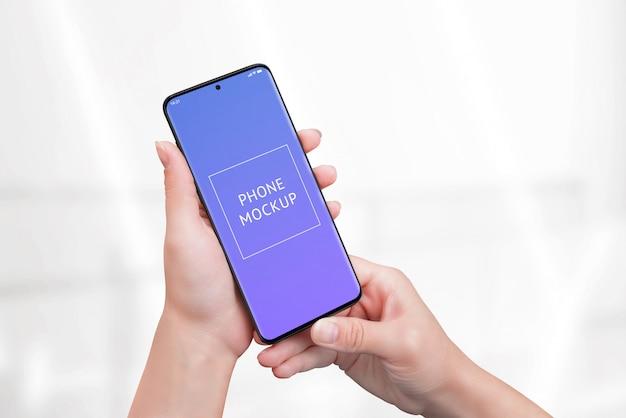 女性の手で電話のモックアップ。 Premium Psd