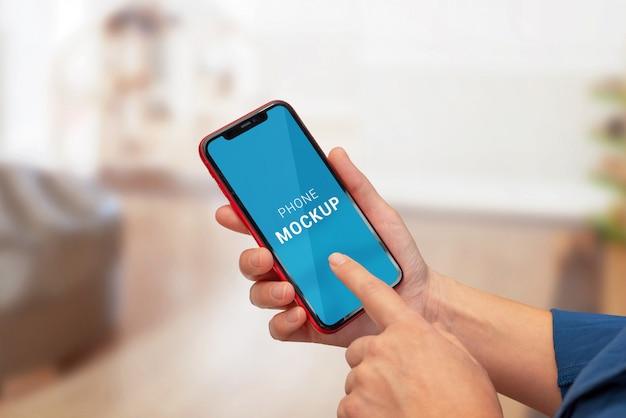 女性の手で水平位置に電話のモックアップ。紫色の抽象的な背景 Premium Psd