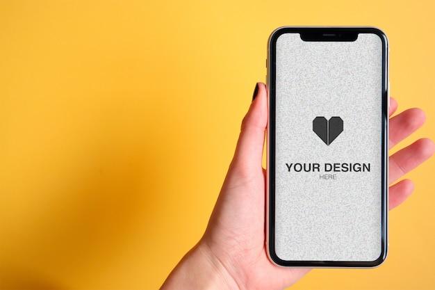 携帯電話を選ぶ手にアプリやウェブサイトのモックアップ Premium Psd