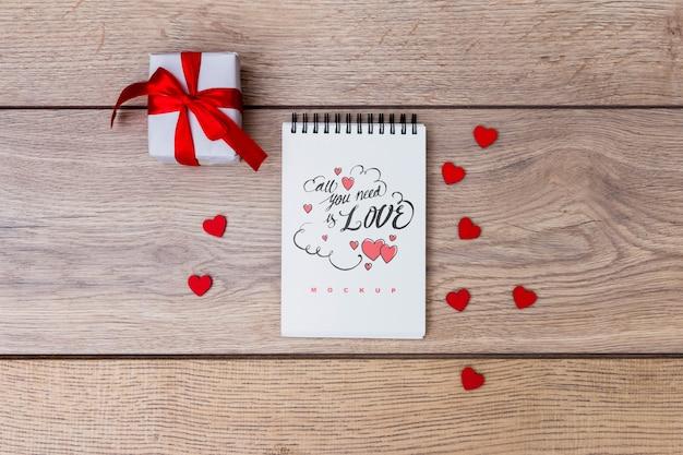 バレンタインのギフトボックスの横にあるメモ帳モックアップ 無料 Psd