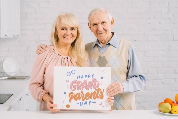 プラカードモックアップを保持している祖父母 無料 Psd