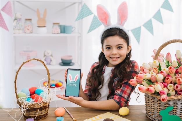イースターの日にスマートフォンのモックアップを持つ少女 無料 Psd