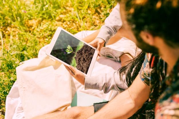 Человек с помощью планшета макет в природе Бесплатные Psd