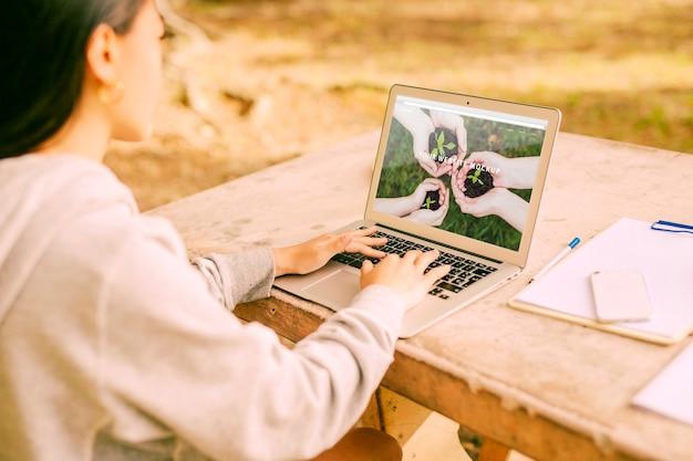 Женщина, используя ноутбук макет в природе Бесплатные Psd