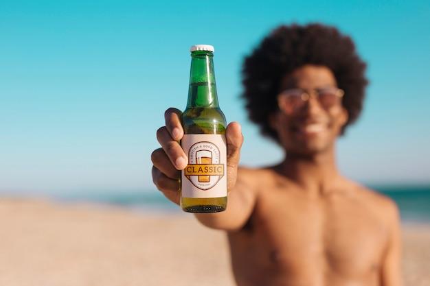 ビーチでビール瓶のモックアップを持つ男 無料 Psd